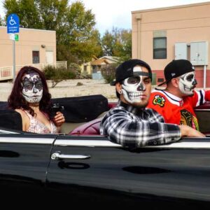 Three people in a lowrider waiting for the Day of the Dead parade to begin