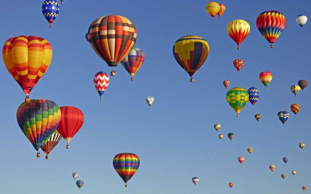 Hot air balloons like ornaments in the sky over Albuquerque