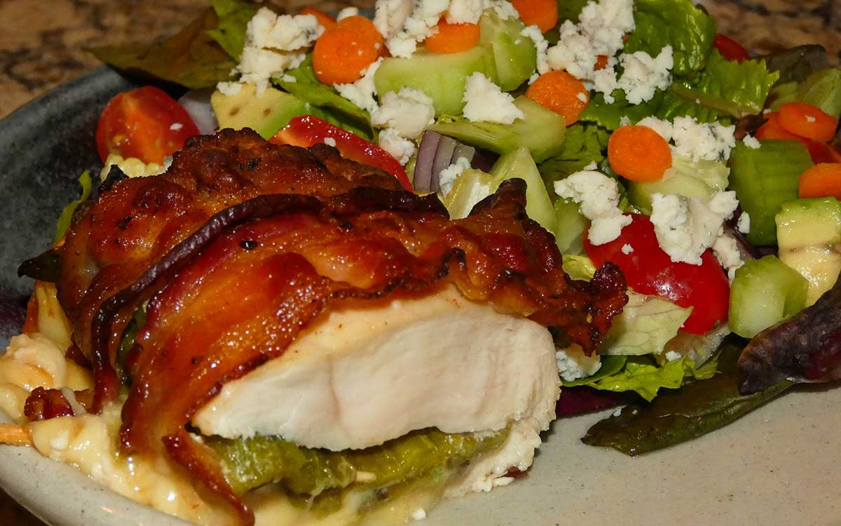 Hatch green chile and cheese stuffed chicken breast wrapped in bacon with a salad
